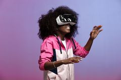Mod young brown-haired curly girl dressed in the pink sports jacket uses the virtual reality glasses in the studio on royalty free stock image