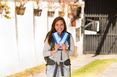 Młoda ładna kobieta jest ubranym przypadkowej odzieży i plecaka pozycję przed kamerą trzyma podróż, ono uśmiecha się szczęśliwie, Obraz Stock