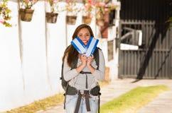 Młoda ładna kobieta jest ubranym przypadkowej odzieży i plecaka pozycję przed kamerą trzyma podróż, ono uśmiecha się szczęśliwie, Fotografia Stock
