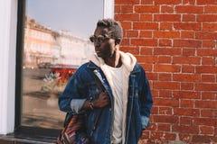 Moda afrykański mężczyzna w cajg kurtce z plecaka odprowadzeniem na miasto ulicie, zdjęcia stock