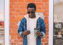 Moda afrykański mężczyzna z smartphone, chwyt filiżanka zdjęcia royalty free