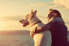 Młoda atrakcyjna dziewczyna z jej zwierzę domowe psem przy plażą Obrazy Royalty Free