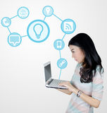 Młoda Azjatycka kobieta używa laptop z technologii ikonami Zdjęcie Royalty Free