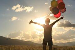Młoda azjatykcia kobieta na zmierzchu obszarze trawiastym z barwionymi balonami Obrazy Stock