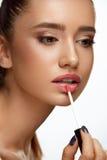 Moda With Beauty Face modelo femenino que aplica protector labial en los labios Imagen de archivo libre de regalías