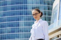 Młoda biznesowa kobieta na tle drapacze chmur Zdjęcia Royalty Free