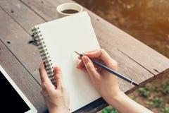 Młoda biznesowej kobiety ręka z ołówkowym writing na notatniku Kobieta Obrazy Stock