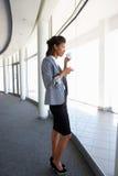 Młoda bizneswoman pozycja W korytarzu Pije kawę Nowożytny budynek biurowy Obraz Royalty Free