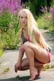 Młoda blondynki kobieta w parkowym przycupnięciu zestrzela Zdjęcia Stock
