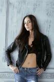 Młoda brunetki kobieta w skórzanej kurtce przy rocznikiem Zdjęcia Stock