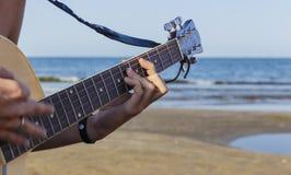 Młoda chłopiec bawić się gitarę akustyczną na plaży Obrazy Stock