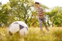 Młoda chłopiec bawić się meczu piłkarskiego ciupnięcia piłkę Fotografia Royalty Free