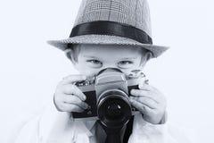 Młoda chłopiec bawić się z starą kamerą być fotografem Fotografia Stock