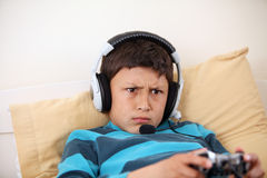 Młoda chłopiec marszczy brwi podczas gdy bawić się wideo grę Obrazy Royalty Free
