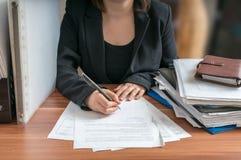 Młoda dama (prawnik) w writing w biurze Fotografia Royalty Free