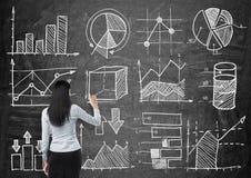 Młoda dama rysuje niektóre wykresy na czarnym chalkboard i mapy Tylni widok model Obraz Stock