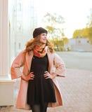 Moda de la calle, mujer hermosa en la capa que presenta en la ciudad Foto de archivo