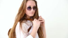 Moda de la juventud moderna muchacha elegante que presenta contra la pared blanca en vaqueros, la camisa blanca, con la mochila y metrajes