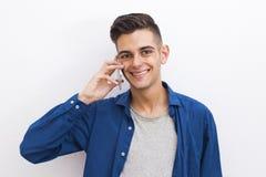 Moda de los jóvenes del retrato que habla el teléfono móvil Imagenes de archivo