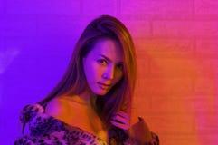 Moda del retrato de una mujer asi?tica en la luz ne?n-violeta y roja que brilla en la oscuridad con belleza y atractivo, atractiv fotografía de archivo