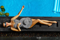 Moda del verano de la mujer Muchacha atractiva que toma el sol por la piscina belleza Fotografía de archivo libre de regalías