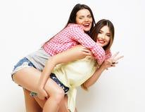Moda dos que ríe a las amigas pintadas que abrazan y que se divierten Foto de archivo