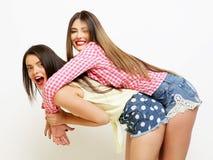 Moda dos que ríe a las amigas pintadas que abrazan y que se divierten Imagen de archivo