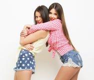 Moda dos que ríe a las amigas pintadas que abrazan y que se divierten Imagen de archivo libre de regalías
