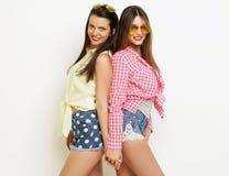 Moda dos que ríe a las amigas pintadas que abrazan y que se divierten Fotografía de archivo