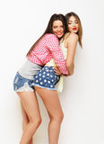 Moda dos que ríe a las amigas pintadas que abrazan y que se divierten Foto de archivo libre de regalías