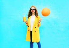 Moda dosyć uśmiecha się kobiety z pomarańczowym lotniczym balonem trzyma filiżankę owocowy sok Obrazy Royalty Free