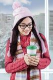 Młoda dziewczyna cieszy się gorącą kawę przy mieszkaniem Obrazy Royalty Free