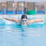 Młoda dziewczyna pływa motyliego uderzenia styl Fotografia Stock