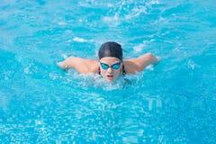 Młoda dziewczyna pływa motyliego uderzenia styl Zdjęcia Stock