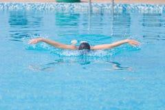Młoda dziewczyna pływa motyliego uderzenia styl Obrazy Royalty Free