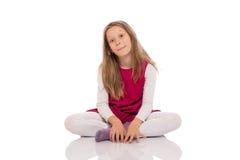 Młoda dziewczyna robi twarzom na podłoga Obrazy Royalty Free