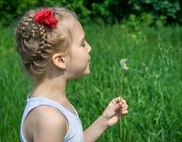 Młoda dziewczyna w parkowym dmuchaniu na dandelion Zdjęcie Royalty Free