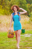 Młoda dziewczyna w słomianym kapeluszu z koszem dzicy kwiaty Obraz Stock