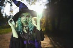 Młoda dziewczyna z zielonym włosy i skóry kostiumem czarownica w lasowym Halloweenowym czasie Zdjęcia Royalty Free