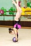 Młoda żeńska gimnastyczka robi podstępnej sztuczce z piłką Fotografia Stock