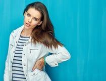 Moda hermosa de la muchacha que presenta en fondo azul de la pared Imagenes de archivo