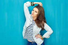 Moda hermosa de la muchacha que presenta en fondo azul de la pared Foto de archivo libre de regalías