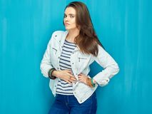 Moda hermosa de la muchacha que presenta en fondo azul de la pared Fotos de archivo libres de regalías