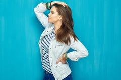 Moda hermosa de la muchacha que presenta en fondo azul de la pared Fotos de archivo