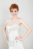 Młoda i piękna rudzielec panna młoda ubierał ślubną suknię pozuje w studiu Obrazy Royalty Free