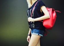 Moda i styl modny czerwony plecak nad jego ramieniem przy dziewczyną część ciała na ciemnym tle Obrazy Royalty Free