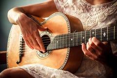 Młoda kobieta bawić się gitarę indoors na słonecznym dniu Zdjęcie Royalty Free