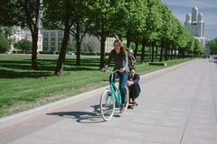 Młoda kobieta ciągnie mężczyzna na deskorolka na bicyklu Fotografia Stock
