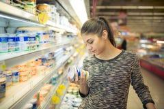 Młoda kobieta czytelniczy składniki, deklaracja lub data ważności na dzienniczka produkcie przed kupować je, Ciekawej kobiety czy Zdjęcia Stock