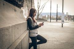 Młoda kobieta patrzeje telefon komórkowego Obrazy Royalty Free